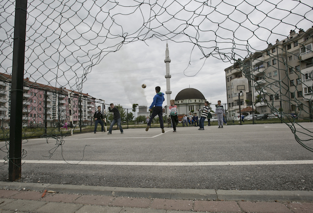 A soccer match in front of the apartment buildings where many villagers evicted from Hade now live. [Visar Kryeziu/ICIJ]
