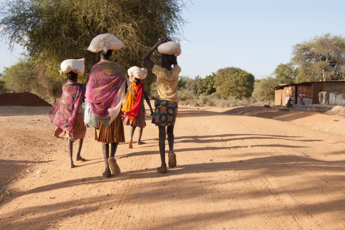 African girls leave the market carrying bags with food