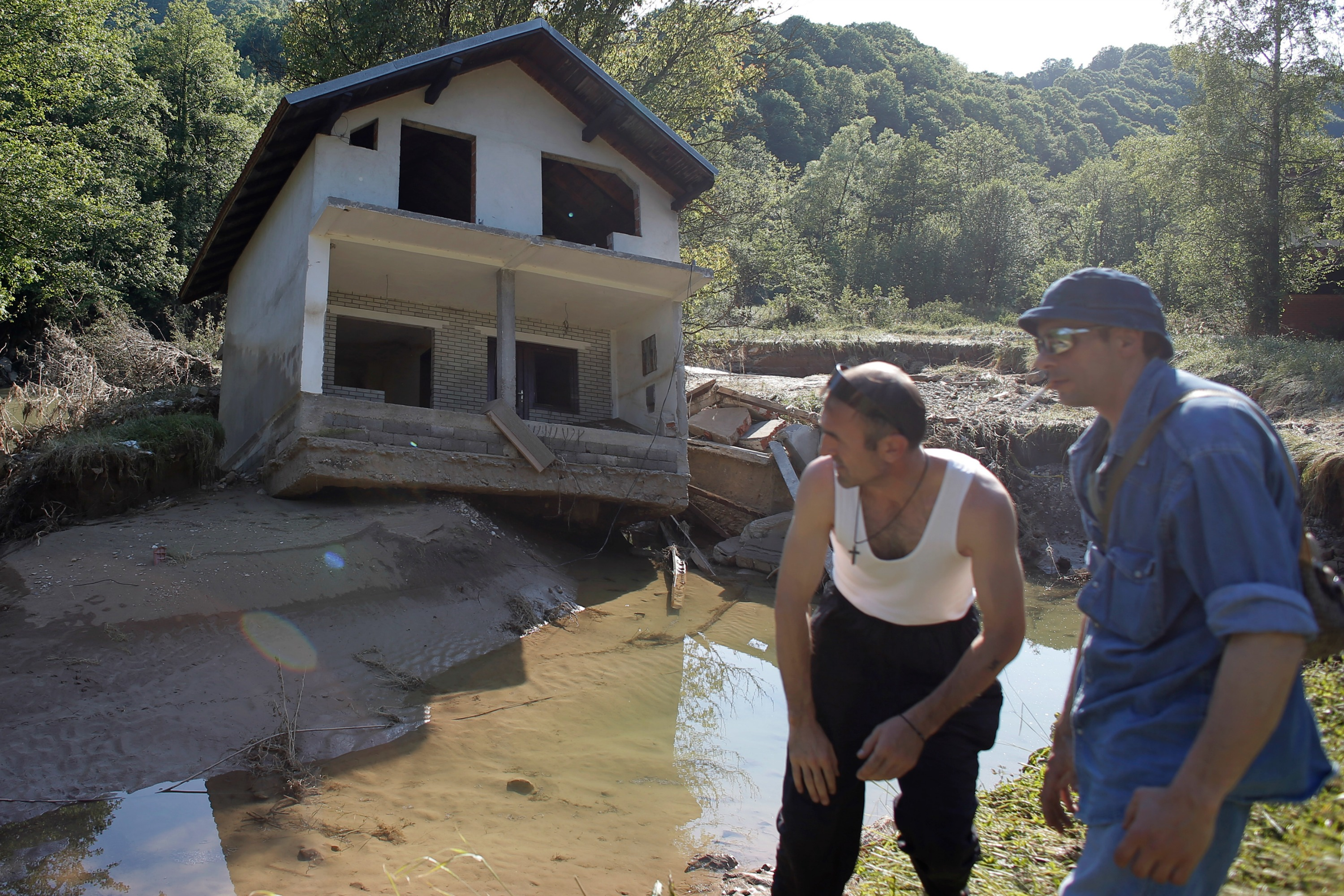 Two men stand near a house tilted by floods in the town of Valjevo, southwest from Belgrade, 21 May