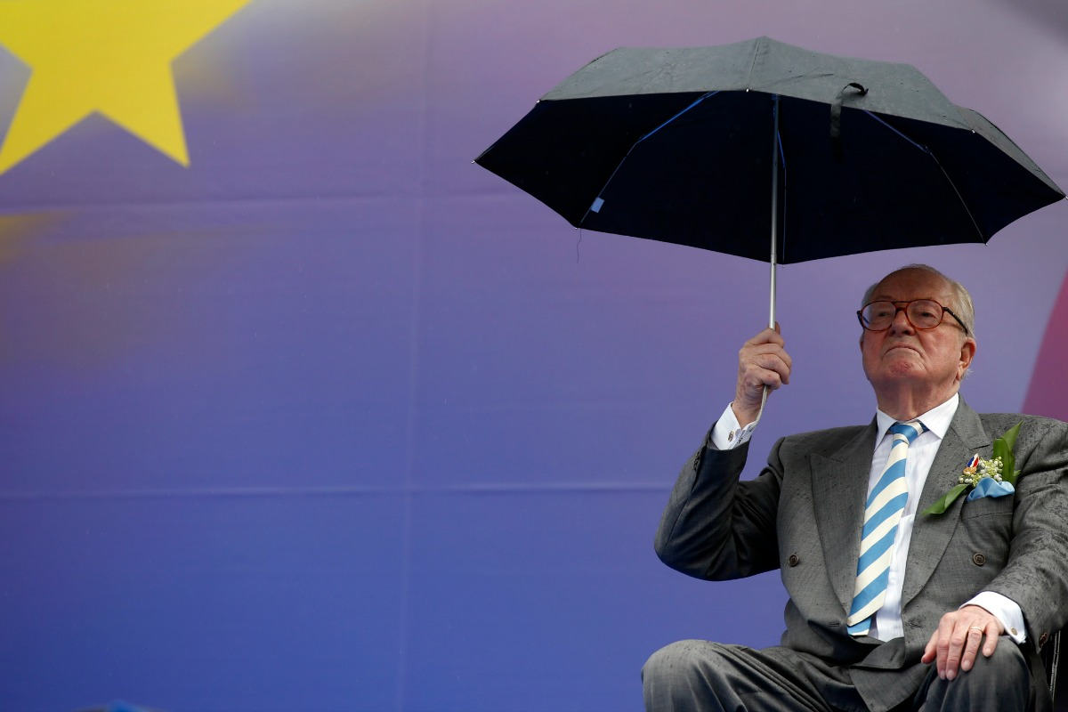 Jean-Marie Le Pen, France's National Front political party founder, holds an umbrella as he attends their traditional rally in Paris May 1, 2014. [REUTERS/Benoit Tessier]