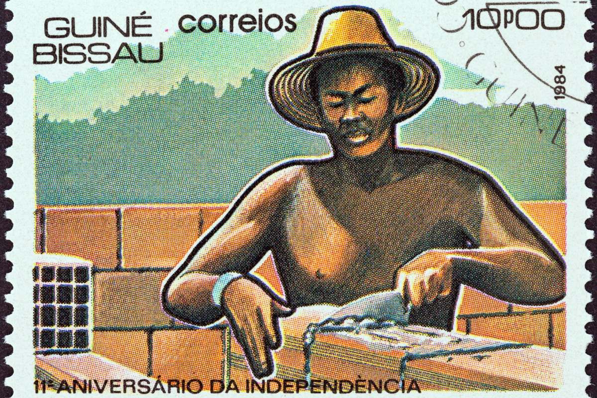 "A stamp printed in Guinea-Bissau from the ""11th anniversary of Independence"" issue shows laying bricks, circa 1984 [Photo: Shutterstock]"
