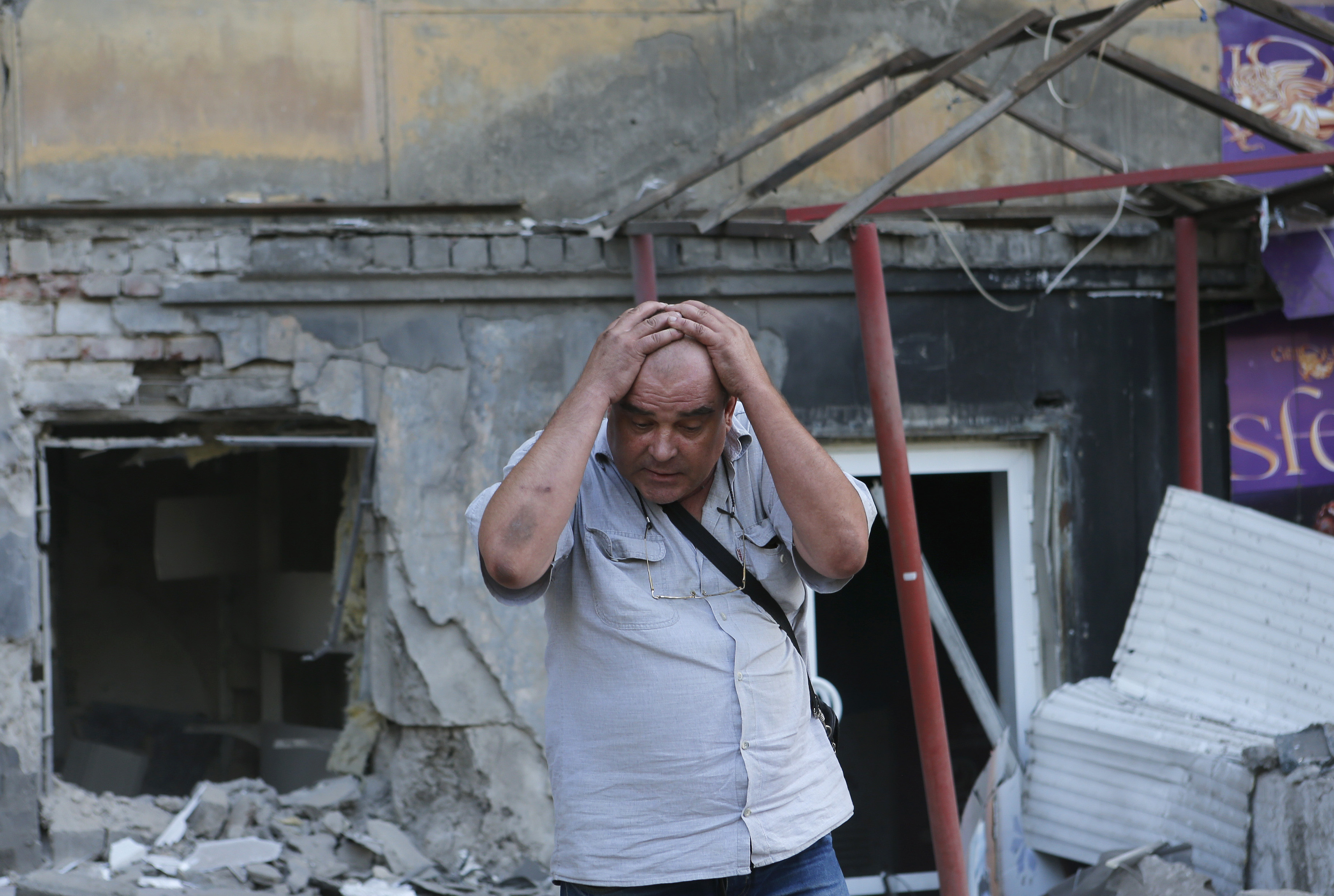 A man reacts as he stands in front of a building damaged by recent shelling by Ukrainian forces, in Donetsk,20  August 2014. REUTERS