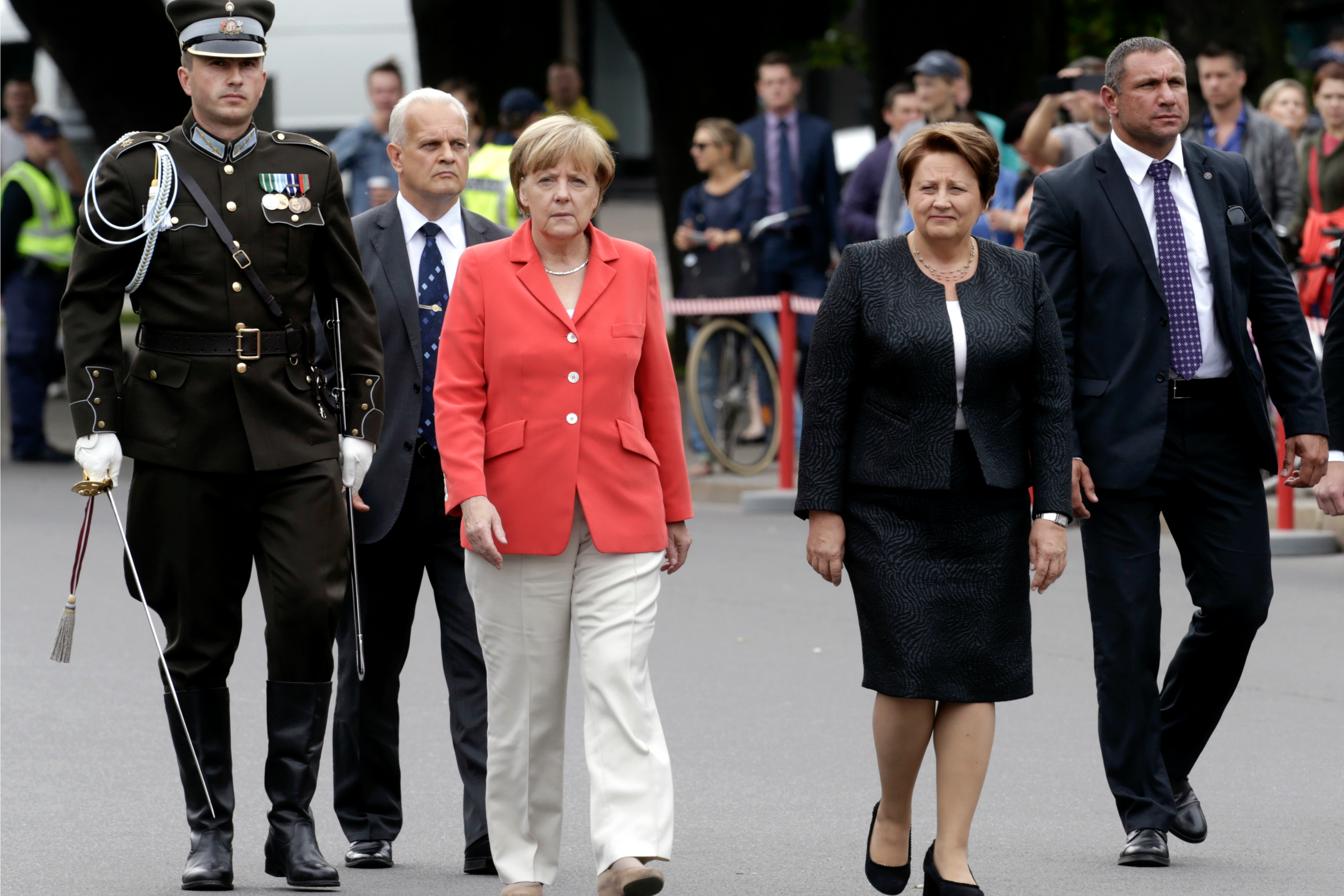 Latvia's Prime Minister Laimdota Straujuma and Germany's Chancellor Angela Merkel arrive to attend a wreath-laying ceremony in Riga, 18 August 2014. REUTERS